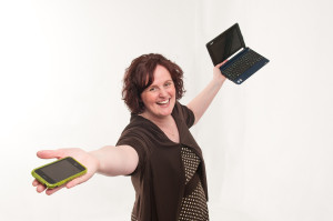 Angela Crocker holding an iPhone and laptop