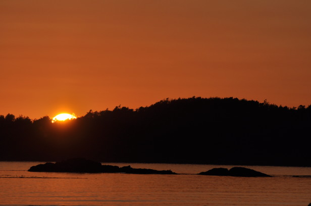 Sun sets behind a small island at the beach in Tofino, BC.