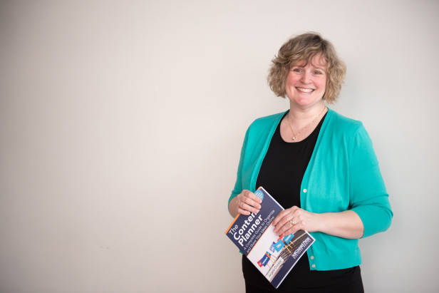 Angela Crocker holding a copy of her book, The Content Planner.